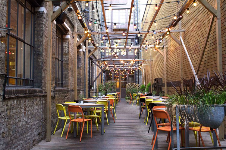 Lime green and orange chairs with brown tables at outside Bermondsey restaurant with fairy lights above