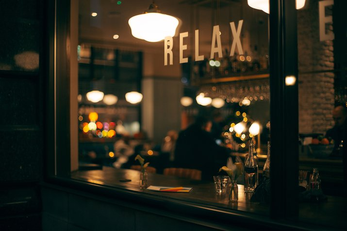 Looking through a bar window that says 'Relax' with a blurred bar and table and chairs inside