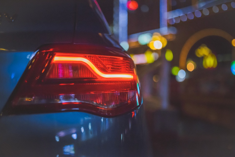 Close-up of the right-hand side back end of a car, focusing on the light, taken in the evening