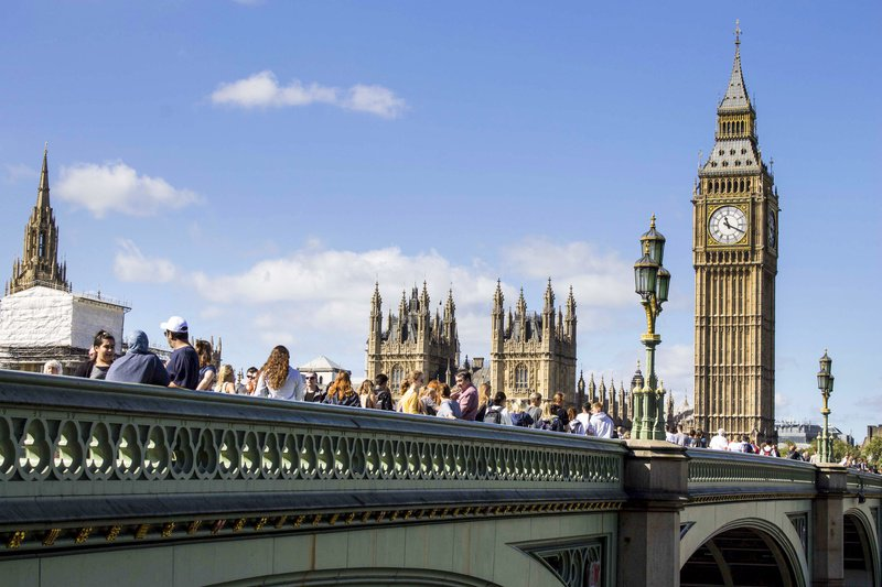 Westminster Bridge with lots of people on it and Big Ben in the background, taken from below the bridge