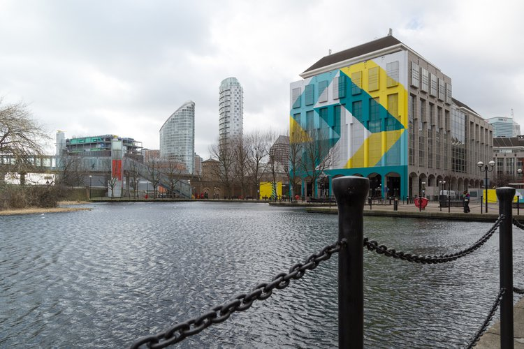 Side of building decorated in turquoise, yellow and white colours, overlooking the water in Royal Victoria