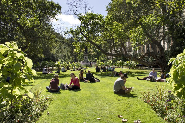 People sitting in Whitehall Gardens park near Embankment on a sunny day enjoying the good weather