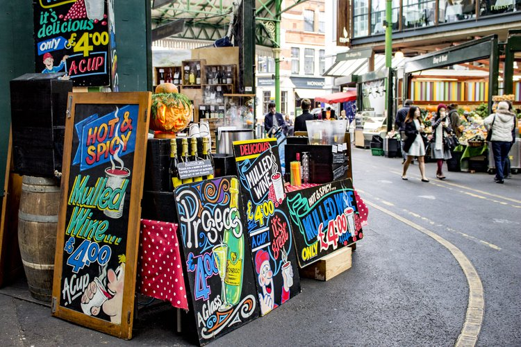 Colourful black board signs promoting food and drink deals at Borough Market in London Bridge