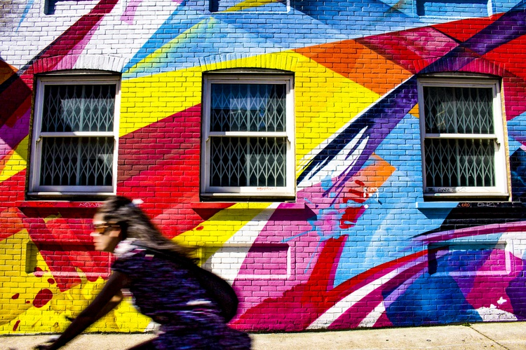 Building decorated randomly in lots of bright colours while a girl cycles past