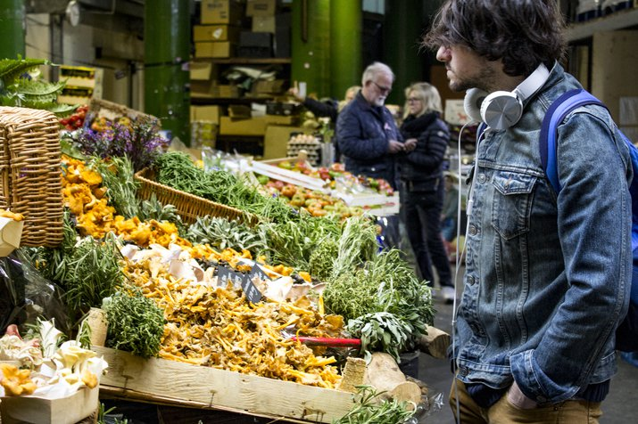 A trendy young man with headphones looking at a vegetable stand at Borough Market, London