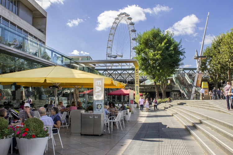A sunny day in South Bank with EAT's yellow umbrellas and tables and chairs outside where people are eating, with the London Eye in the background