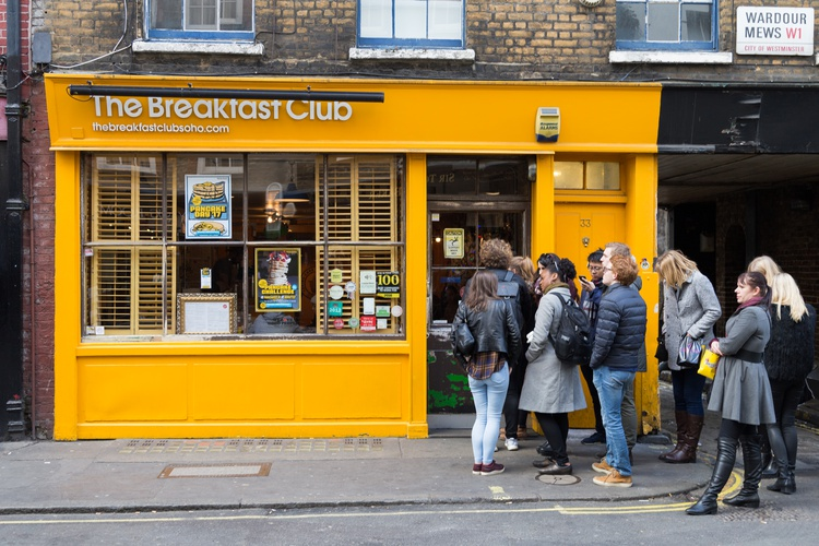 Yellow shop-front of The Breakfast Club in Soho with people queuing up outside to enter