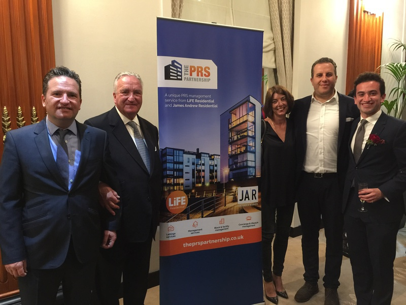 Our MD, Jonothan Werth, his wife, Joey Barnett, and 2 other men stand smiling stood by a PRS Partnership pull-up banner