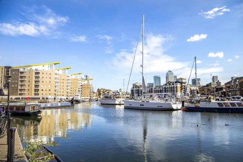 A view across the Royal Docklands area with boats on the water with houses around it and London city skyscrapers from Canary Wharf shown in the background
