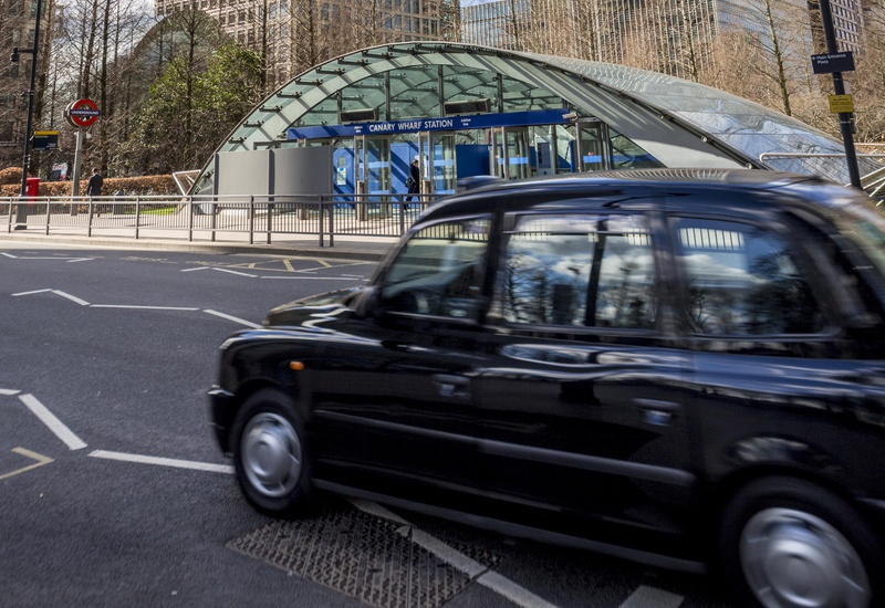 Outside of Canary Wharf station, looking at the station from across the road with a moving black taxi in between