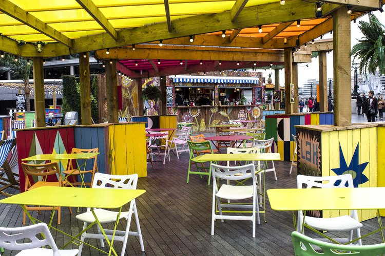 Outside brightly coloured tables, chairs and deck chairs, under canopies along Shad Thames, London Bridge